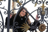 Brunette woman near wrought fence — Stockfoto