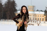 Young woman in fur jacket in park — Stock Photo