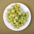 Grapes in a white plate on a green background — Zdjęcie stockowe