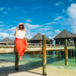 The girl on a wooden bridge near the water bungalows (Maldives - — Stockfoto