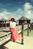 Girl on a wooden bridge near the water bungalows — Stock Photo
