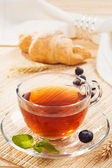 Cup of tea and a croissant for breakfast — Stock Photo