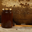 Honeycomb with fresh honey in a vase on wooden table. — Stock Photo #31809375