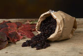 Black raisins in paper bags on a wooden table — Stock Photo