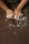 Woman's hands kneading dough on wooden table — Stock Photo