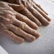 Old womans hands, reading a book with braille language — Stock Photo
