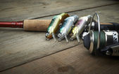 Colorful lures with the fishing rod on the wooden pier — Stock Photo