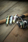 Iscas coloridas com a vara de pescar no píer de madeira — Fotografia Stock