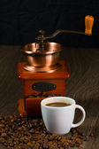 Coffee antique grinder, coffee beans and cup of coffee. — Zdjęcie stockowe