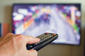 Hand holding TV remote control with a television in the background. — Stock Photo