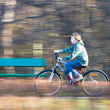 Royalty-Free Stock Photo: Mountain biking in a park - Young biker on a park biking trail going fast (motion blurred image)