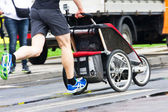 Father run with baby stroller in marathon — Stock Photo