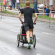 KRAKOW, POLAND - APRIL 28 : CracoviMarathon. Wladyslaw Wachulec with his son in wheelchair on city streets on April 28, 2013 in Krakow, POLAND — Stock Photo #25099687