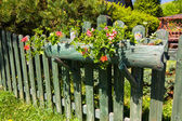 Beautiful flower decoration of an old wooden fence — Stock Photo