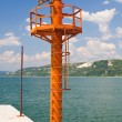 Small red lighthouse on harbor entrance of Balchik, against great blue sky with waves crashing the shore — Stock Photo