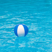 White and blue beach ball floating on a sparkling blue swimming pool — Stock Photo