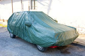 A parked car with protective cover — Stock Photo