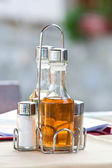 Bottles with olive oil, vinegar, salt and pepper on the table in restaurant — Stock Photo