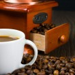 Coffee antique grinder, coffee beans and cup of coffee. — Stock Photo #30787665