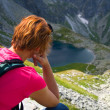 Woman sitting on mountain top and admiring mountain landscape — Stock Photo