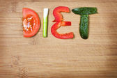 Vegetables on the cutting board and word diet over wooden background — Stock Photo