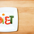 Plate with vegetables and word diet over wooden background  — Stockfoto