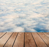 Empty wooden deck table with clouds. Ready for product montage display. — Stockfoto