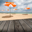 Beach umbrellas on the white sand and empty wooden deck table. — Stock Photo