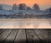 Winter sunrise over the river and empty wooden deck table. — Stock Photo