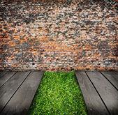 Interior com parede de tijolos e grama verde — Foto Stock