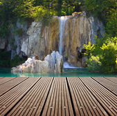Waterfall and empty wooden deck table. Ready for product montage display. — Stock Photo