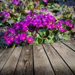 Violet flowers and empty wooden deck table. — Stock Photo