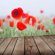 Field of poppies and empty wooden deck table — Stock Photo