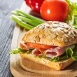 Fresh ham sandwich on wooden board - close up — Stock Photo