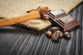 Chocolate bar and spices on wooden table — Stock Photo