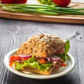 Ham sandwich with lettuce on wood background — Stock Photo
