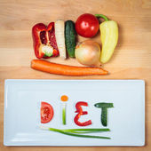 Plate with vegetables and word diet over wooden background — Stock Photo