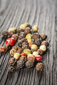 Pepper corns on a wooden board — Stock Photo