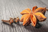 Anise stars and cloves on wooden background — ストック写真