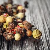 Pepper corns on a wooden board — Stock Photo