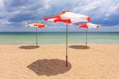 Beach umbrellas on the beach with cloudy blue sky — Stock Photo