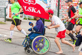 KRAKOW, POLAND - MAY 28 : Cracovia Marathon. Unidentified handicapped man in  marathon on a wheelchair on the city streets on May 18, 2014 in Krakow, POLAND  — Stock Photo