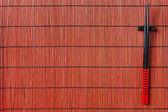 Two chopsticks on sushi mat background — Stock Photo