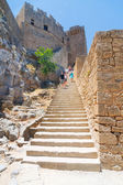 LINDOS, GREECE - JUNE 24: Unidentified tourists walking in historic town Lindos on June 24, 2008. Lindos is most popular turist destination located in the Rhodes Island, eastern Aegean Sea. — Stockfoto