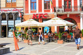 BRASOV, ROMANIA - JULY 15: Council Square on July 15, 2014 in Brasov, Romania. People buying fried chicken at local Kentucky Fried Chicken Restaurant. — ストック写真