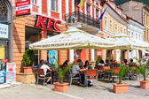 BRASOV, ROMANIA - JULY 15: Council Square on July 15, 2014 in Brasov, Romania. People buying fried chicken at local Kentucky Fried Chicken Restaurant. — Foto Stock