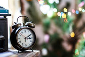 Old style alarm clock on a table with blurred background — Stock Photo