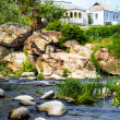Mountain river with mossy stones.  house on the rock. — Stock Photo