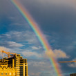 Stock Photo: Photo of bright colorful rainbow over city, sun shining in rainy day, beautiful colors phenomenon in dark blue sky, overcast weather, nature landscape in town, autumn, gh