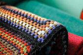 Rolled handmade crochet afghan blanket of granny squares. Rainbo — Stock Photo